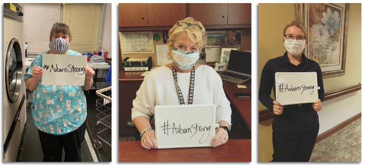 Auburn Homes & Services employees holding #AuburnStrong signs.
