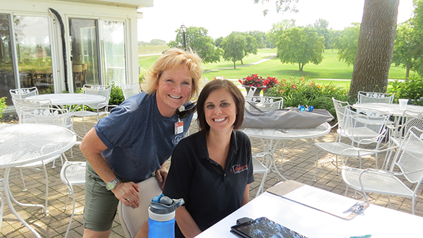 two women working at Auburn Golf Tournament